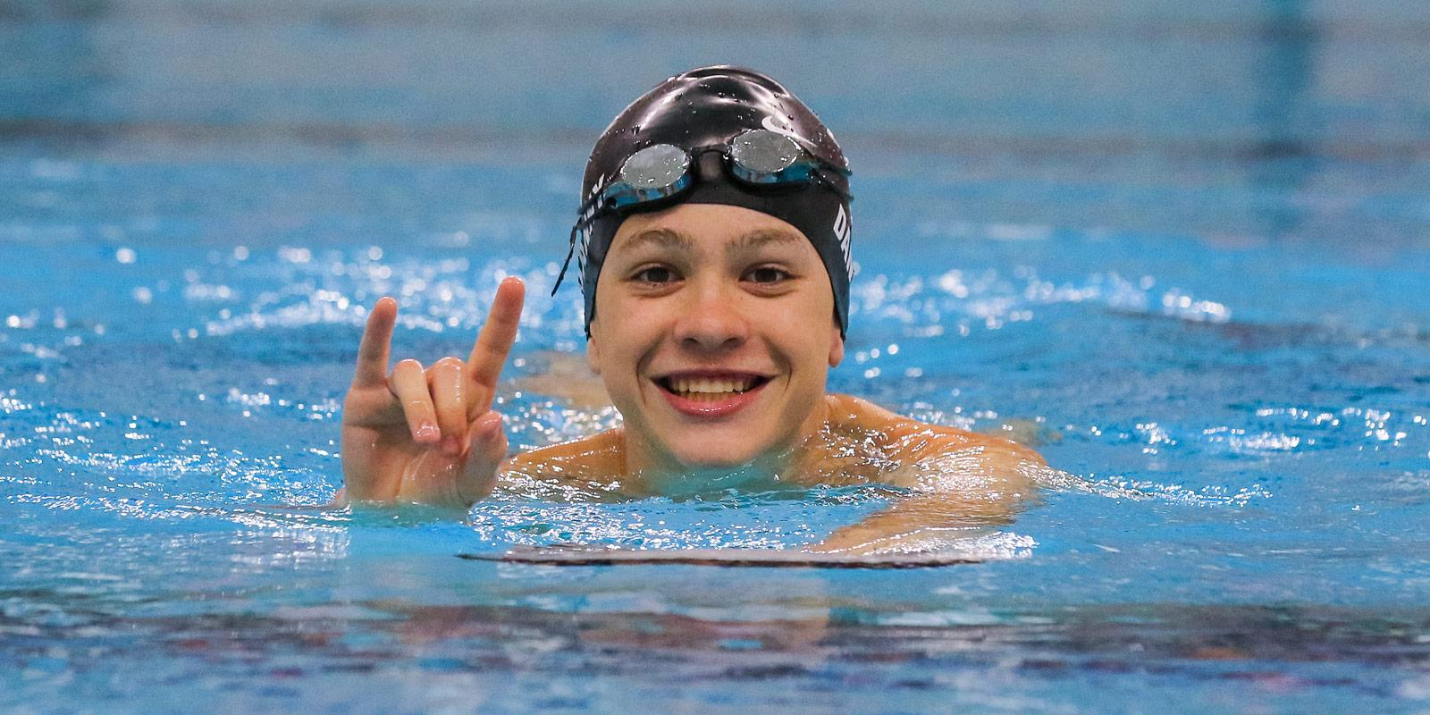 A young swimmer shows his Longhorn pride